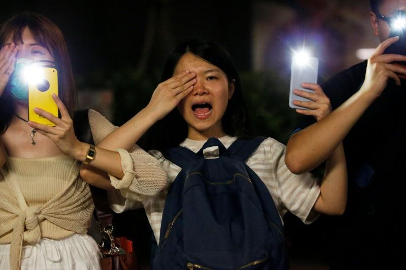 晚間9點左右,現場港人紛紛以右手遮眼響應#Eye4HK、左手拿著手機,還有人大喊「黑警還眼」。(路透)