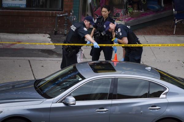 加拿大警方在案發現場檢查彈孔。(美聯社)