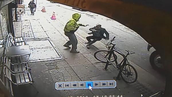 美國洛杉磯有名男子走在人行道上,突然遭另一名男子一把推向車道,撞上行駛而來的大卡車。(圖擷取自監視器畫面)