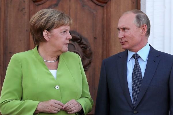 俄羅斯總統普廷(圖右)18日晚間前往德國柏林,與德國總理梅克爾(圖左)會晤。(彭博)