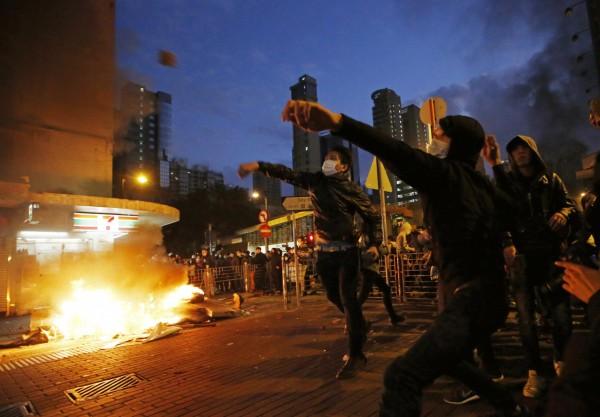 香港旺角的抗議民眾向警方投擲磚塊、在垃圾桶放火。(美聯社)