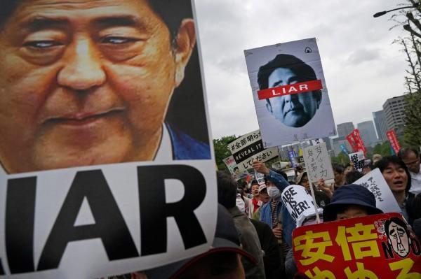 安倍晉三支持率僅剩37%,不支持率高達52.6%,更有抗議民眾在國會議事堂外大罵「安倍騙子」。(彭博)