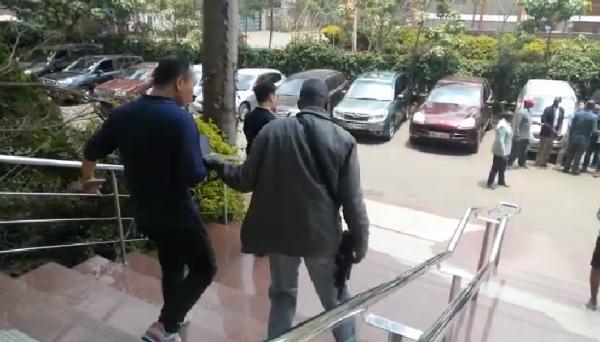 穿著便服、手持武器的肯亞警察,把中國員工趕上車。(圖取自citizentv.co.ke)