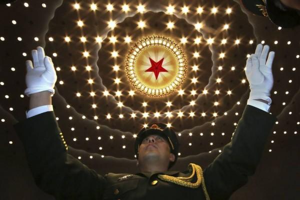 中國政府正在考慮一項計畫,將阿里巴巴和騰訊等科技巨頭回歸國內股市,扭轉中國企業多年來的海外上市潮。圖為在北京舉行的全國人民代表大會上,一名軍事指揮官向樂隊發起指揮命令。(美聯社資料照)