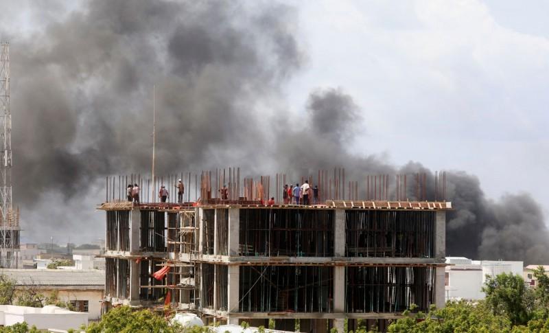 索馬利亞首都發生爆炸案,圖為一群工人當時在附近的建築工地上看著煙霧繚繞。(路透)