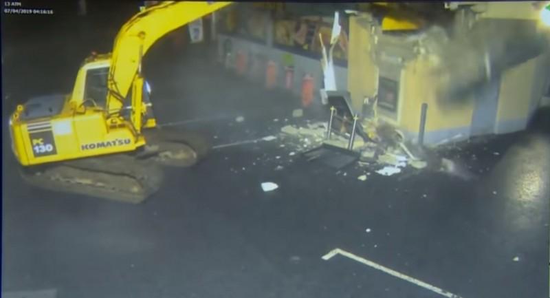 挖土機先是對加油站的牆壁一陣猛挖。(圖擷自The Duck YouTube)
