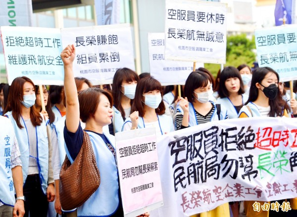Members of three flight attendants' associations yesterday stage a protest in front of the Civil Aeronautics Administration in Taipei, accusing EVA Airways of forcing its flight attendants to work overtime. Photo: Peter Lo, Taipei Times