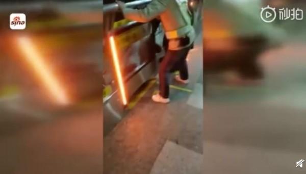 上海地鐵昨一名女乘客擅自翻越電動閘門,結果被夾在電動閘門和列車中間,最後不幸身亡。(圖擷取自新浪新聞)