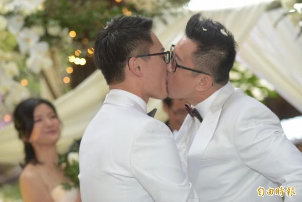同志情侶蔡意欽(右)與佑佑(左)8日在親友的祝福下,由牧師證婚,完成終生大事,兩人相互親吻。(記者張嘉明攝)