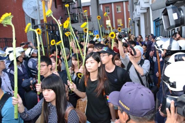 圖為太陽花學運,佔領議場的學運成員手持向日葵,慢慢撤離立院區域。(資料照,記者吳柏軒攝)