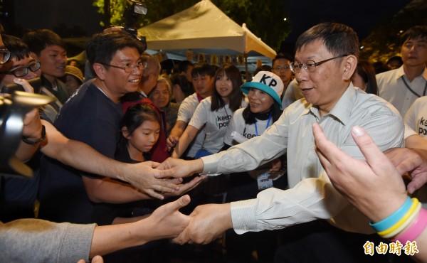 姚人多認為,台北市長柯文哲脫口而出「台灣有些女性不化妝直接上街嚇人」,當一個人說什麼都被預先允許時,台灣的民主體制就會出現破口。圖為柯P舉辦行動競選總部開幕園遊會,與熱情支持者握手致意。(記者劉信德攝)
