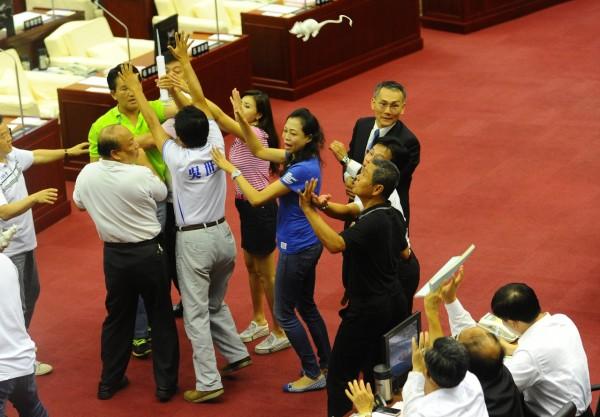 議員童仲彥(左),將老鼠丟向官員席,郝龍斌不為所動,一旁的副市長丁庭宇和秘書長陳永仁出手擋老鼠。(記者張嘉明攝)