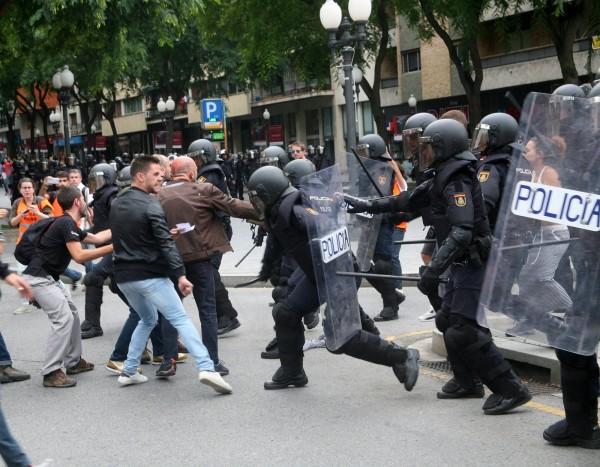 西班牙鎮暴警察在巴賽隆納和其他地區試圖沒收選票和投票箱,用警棍和橡膠子彈驅離阻礙民眾。(歐新社)