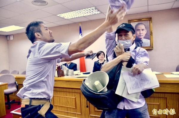 有抗議民眾混入司法法制委員會,突然拿出大聲公與抗議紙板,試圖衝向尤美女,大喊「停止審查、交付公投」等口號,警察隨後將抗議者拉出會議室。(記者羅沛德攝)