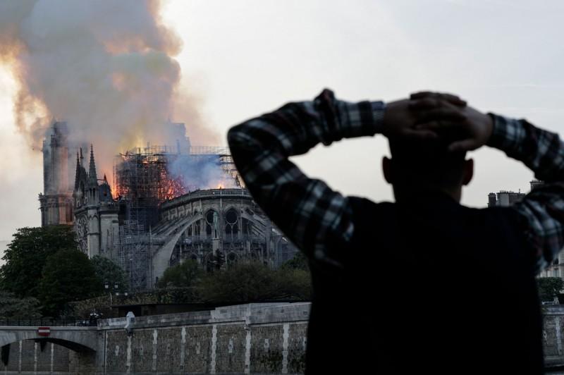 巴黎街上的人們,眼睜睜的看著這棟已有850年歷史的古蹟在火海之中掙扎。(法新社)
