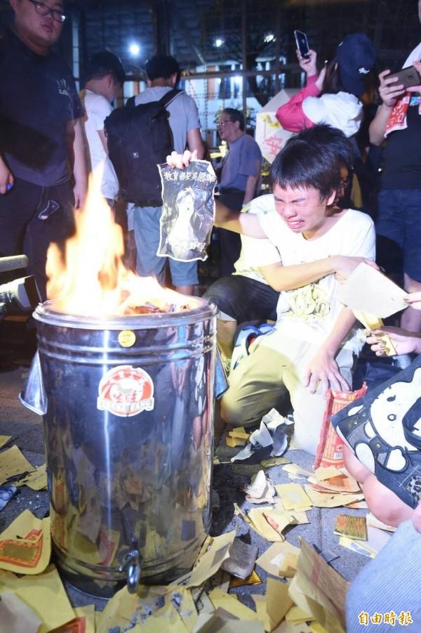 學生將原黏在牆上的抗議文宣一張一張撕下,送到鋼桶內焚化。(記者劉信德攝)