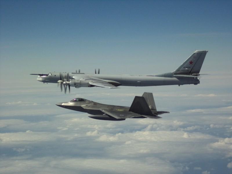北美航空司令部表示,俄羅斯轟炸機(後)20日進入阿拉斯加防空識別區,美方F-22(前)攔截。(圖擷取自臉書_NORAD)