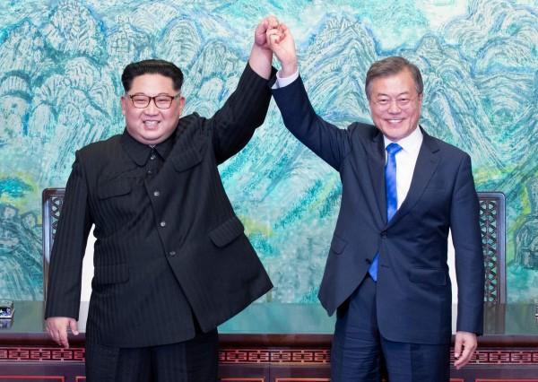 文在寅(右)與金正恩在簽署板門店宣言後,高舉緊握的雙手合照。(法新社)