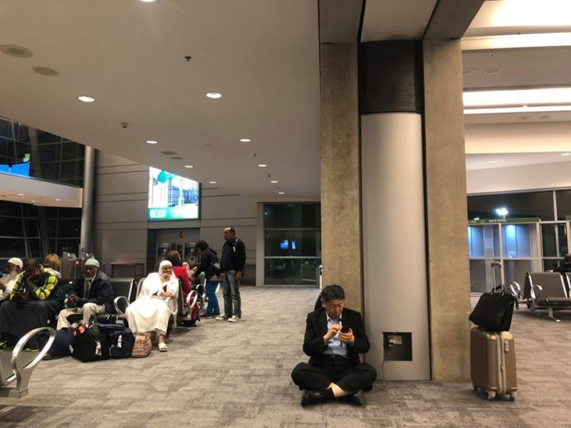 柯文哲為幫手機充電,在機場席地而坐。(圖片取自柯文哲臉書)
