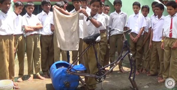 一名印度的10歲男童,由於家中貧困,無法買洗衣機,他卻憑著智慧及創意,利用腳踏車做出了一台人力滾筒洗衣機。(翻攝自youtube)