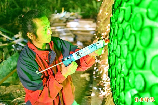 Artist Yang Tsung-hsun applies silicone to a sculpture made of beer bottles and wood on the site of the Taiwan Lantern Festival in the Dapeng Bay National Scenic Area in Pingtung County's Donggang Township on Jan. 31. Photo: Tsai Tsung-hsien, Taipei Times
