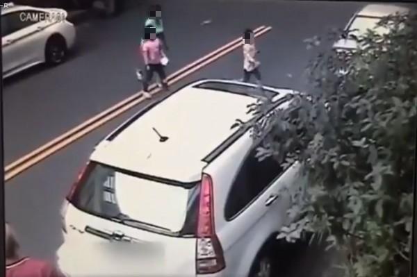 錄影畫面中,一男一女先帶著女童過馬路。(圖擷取自爆料公社影片)