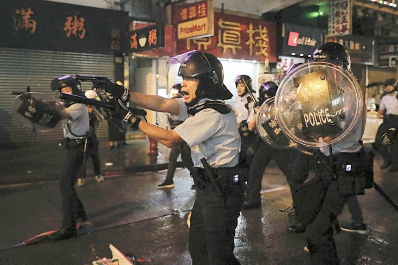 Policemen pull out their guns after a confrontation with demonstrators in Hong Kong's New Territories last night. Photo: AP