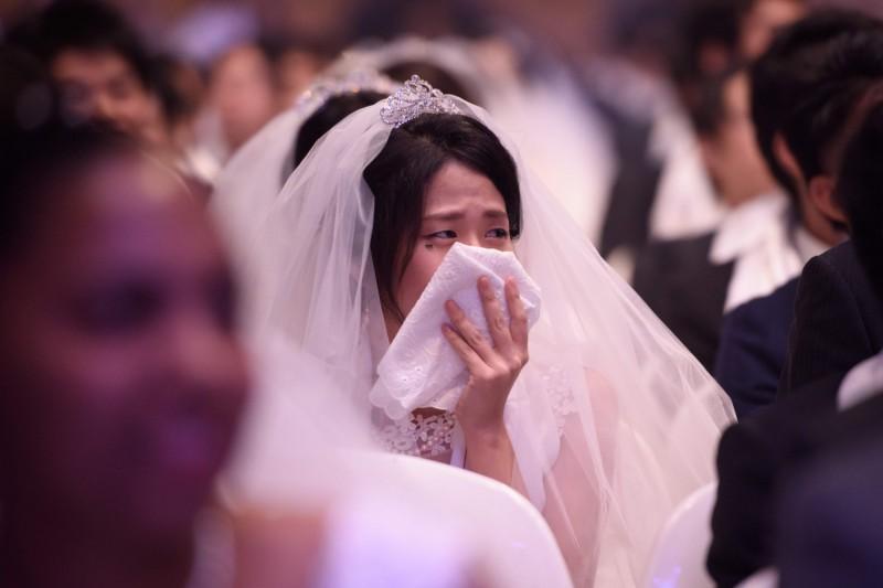 韓國年輕人延遲結婚或放棄結婚的主因,在於無法負擔房價。圖為1名南韓新娘在集體婚禮上哭泣。(法新社)