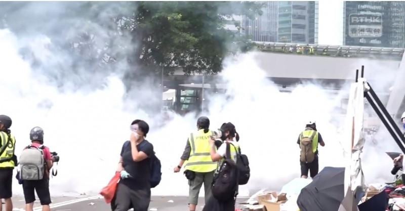 現場一片煙霧瀰漫,示威群眾與記者紛紛走避。(圖擷自香港電台視像新聞 RTHK VNEWS)