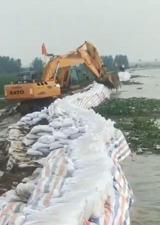 插有中國五星旗的挖土機正在開挖鄱陽湖的堤防。(圖截自微博影片)
