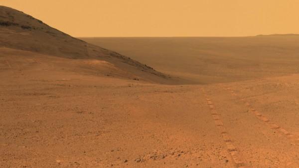 火星地表一片黃土,遠方天空可見漫天沙塵。(擷取自NASA)