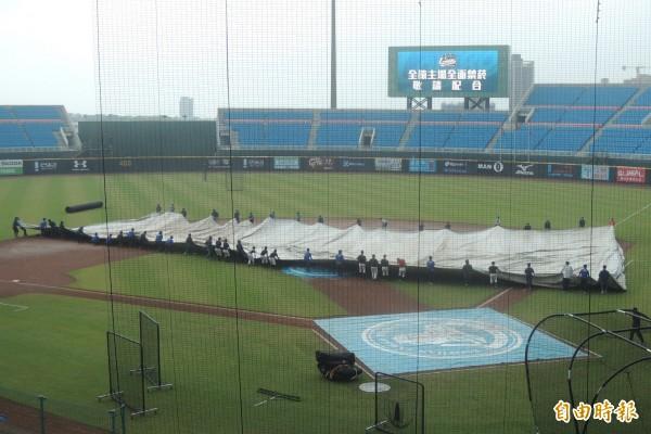 圖為桃園球場遇突降驟雨,聯盟場務人員趕緊拉開防水帆布保護內野。(資料照,記者徐正揚攝)