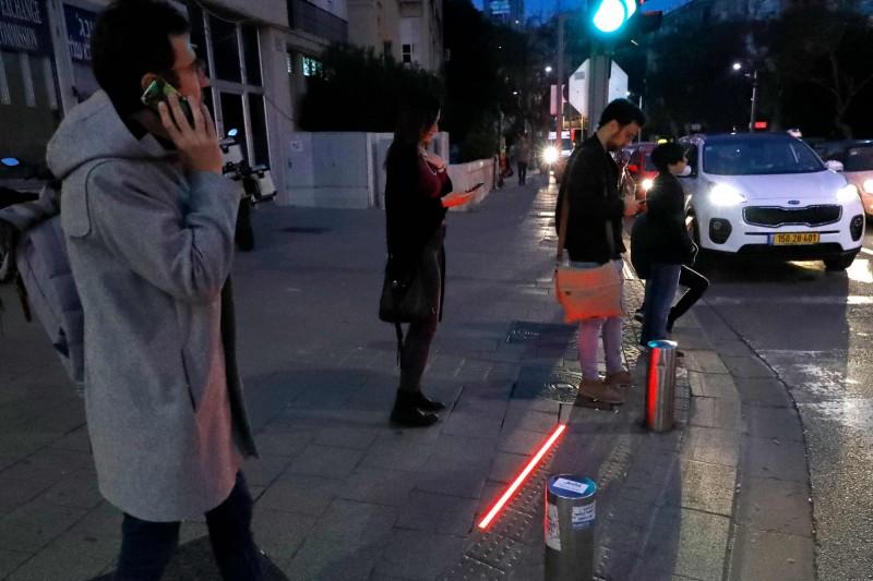當地面上的「紅燈」能不能提醒低頭族注意交通安全,仍待驗證。(法新社)