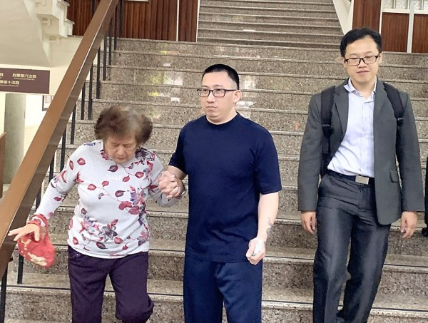 Hsieh Chih-hung, center, who spent 19 years on death row for double homicide, holds his mother's hand as he departs the Tainan branch of the Taiwan High Court yesterday. Photo: CNA