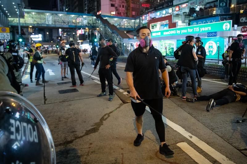 香港銅鑼灣11日晚間出現多名打扮狀似示威者,但手持伸縮警棍的黑衣人,被認為是香港警方假扮示威者,從中挑起衝突。(彭博)