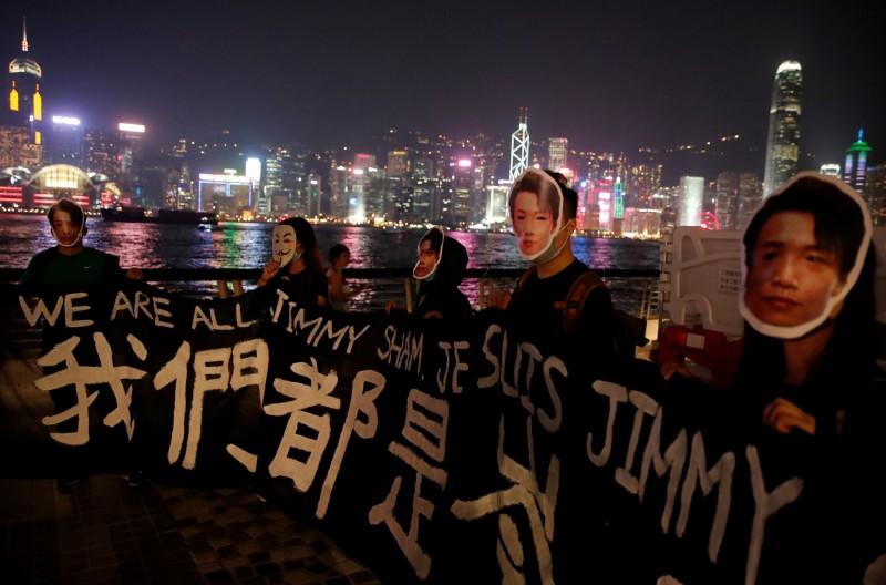 有示威者戴上日前遇襲的「民間人權陣線」(民陣)召集人岑子杰面具,拉著「我們都是岑子杰」布條。(路透)