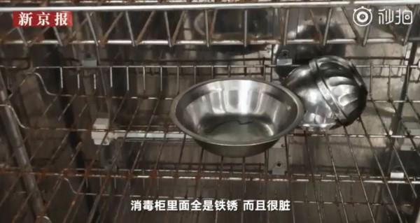 家長指出,小朋友放碗筷的消毒箱不僅髒還都生了鏽。(圖翻攝自《新京報-我們視頻》)