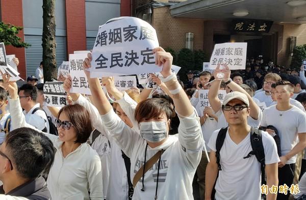翻入立法院的抗議民眾高舉布條,離開立法院。(記者陳志曲攝)
