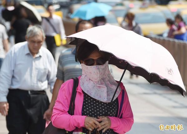中央氣象局觀測,17日台北出現攝氏36度高溫,刷新今年台北高溫紀錄,街頭民眾紛紛撐起陽傘,或拿手中物品遮陽。(記者廖振輝攝)