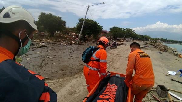 救援人員抬走海邊的遺體。(歐新社)