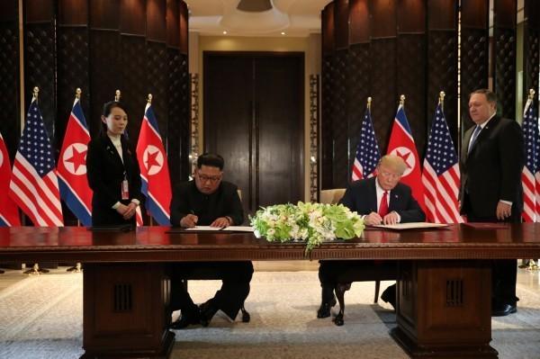 美國總統川普與北韓領導人金正恩共同簽署文件。(路透)