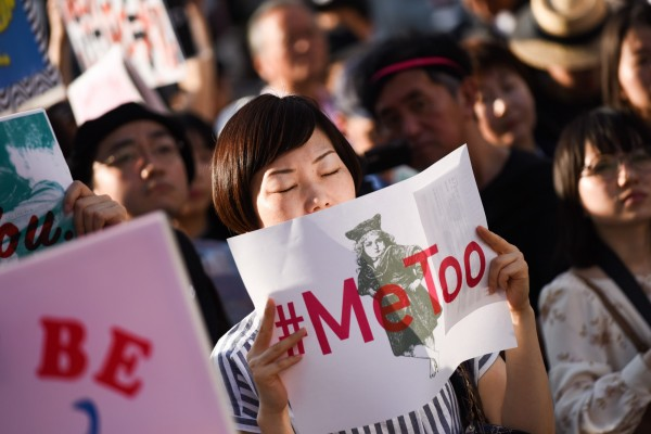 日本一項網路調查結果顯示,僅11%受訪者認為日本「男女平等」。圖為今年4月,日本民眾高舉「#MeToo」標語,抗議政府高官性騷擾女記者。(彭博)