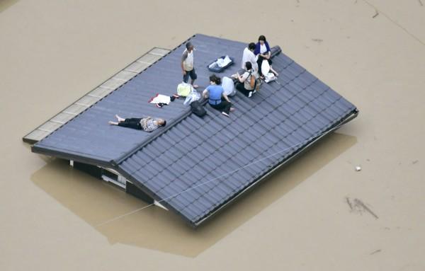 災民在屋頂上等待救援。(路透)