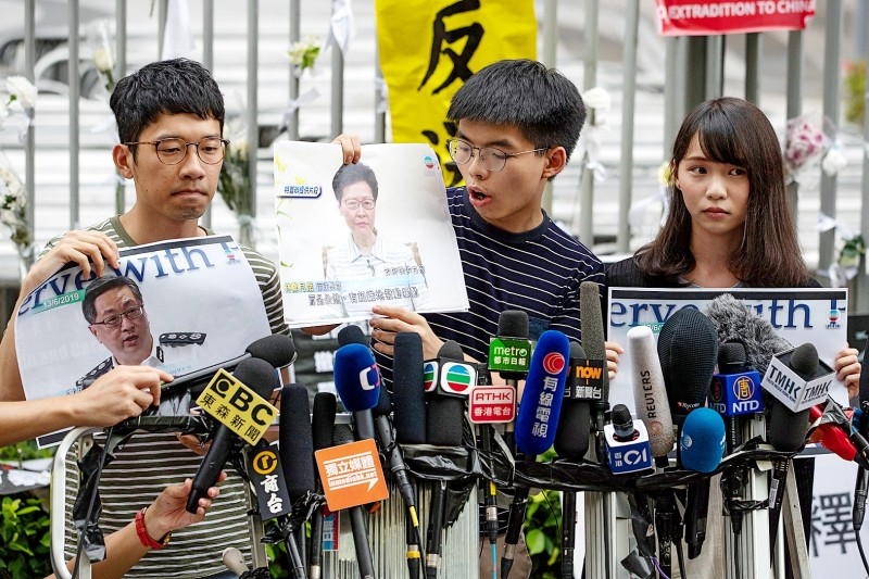 From left, pro-democracy activists Nathan Law, Joshua Wong and Agnes Chow hold a news conference outside the Legislative Council building yesterday to call on Hong Kong Chief Executive Carrie Lam to step down. Photo: EPA-EFE