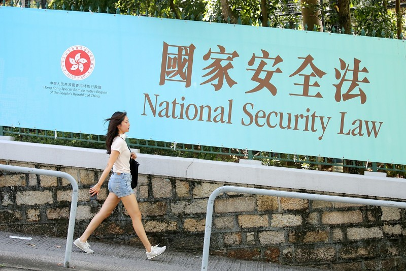 A woman walks past a promotional banner for the national security law for Hong Kong, in Hong Kong yesterday. Photo: AP