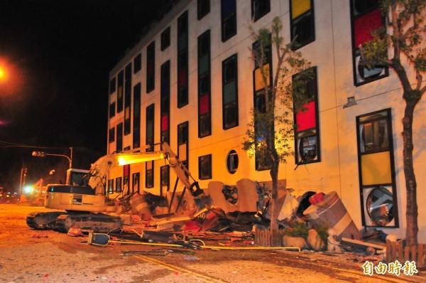 統帥飯店傾斜後,3樓變成1樓,凌晨近3時重機具準備開挖搜救受困者。(記者花孟璟攝)