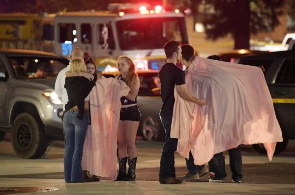 人們逃出酒吧後在街道上相互擁抱安慰。(美聯社)