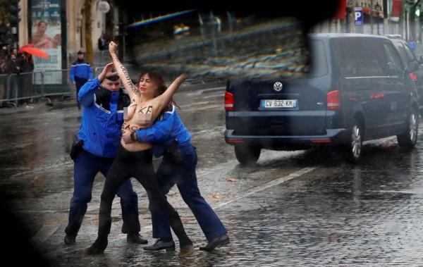 法國一戰100週年活動中,1名裸上半身的女性,一邊高喊著川普是「假和平使者」,一邊衝進川普車隊。(路透)