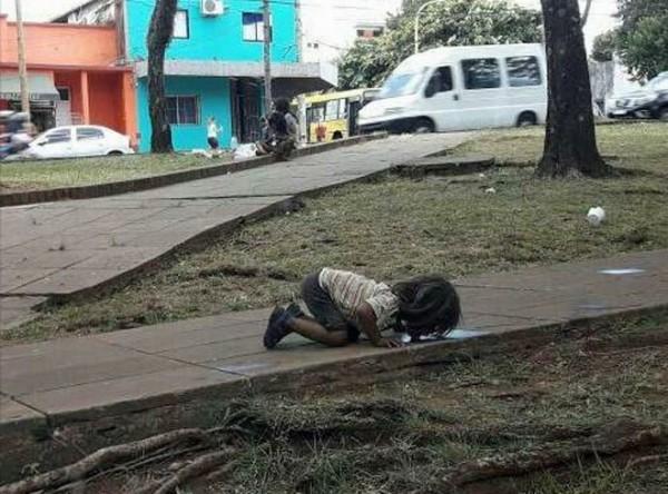 阿根廷波薩達斯(Posadas)最近高溫炎熱,一名女孩可能太渴,被拍到在攝氏38度高溫下跪地舔積水。(圖擷自臉書)