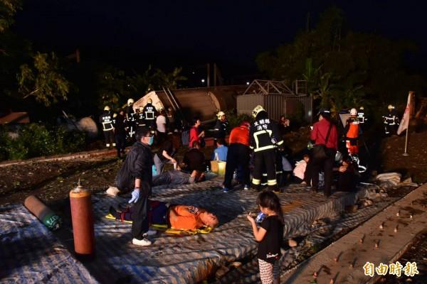 台鐵普悠瑪號列車今天傍晚在宜蘭縣冬山站與蘇澳新站間出軌翻覆,消防人員在現場救治傷患。(記者張議晨攝)